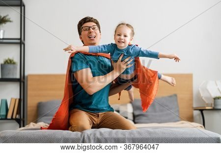Father and his child playing together. Girl and dad in Superhero costume. Daddy and kid having fun, smiling and hugging. Family holiday and togetherness.