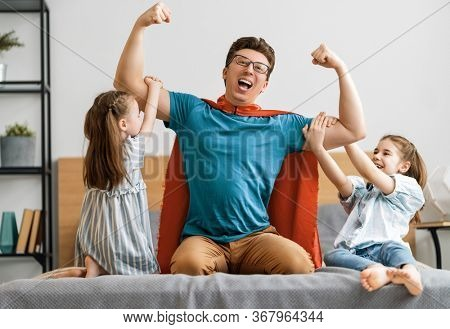 Father and his children playing together. Girls and dad in Superhero costume. Daddy and kids having fun, smiling and hugging. Family holiday and togetherness.