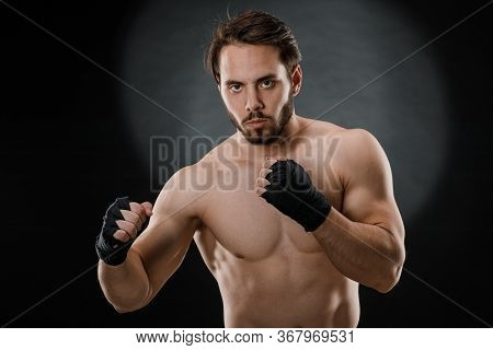 Portrait Of A Boxer With Bandages On His Hands. Fists Of A Fighter Before A Fight Or Training In The