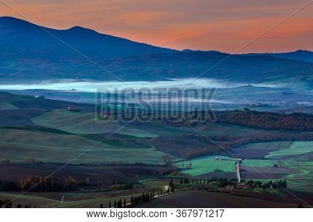 Tuscany. Predawn dusk. Photo taken on a protective wall around the ancient city of Pienza. The concept of active and photo tourism
