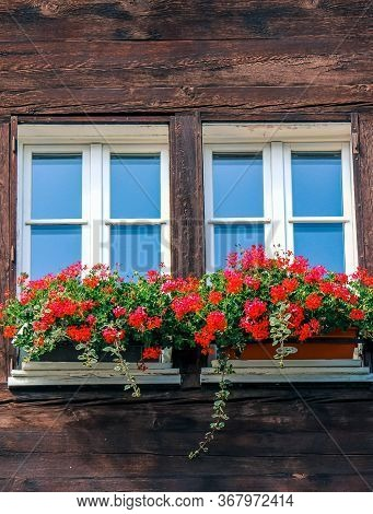 Typical Window Of Wooden Alpine Chalet. Wooden Hut, Red Flowers In Window. Traditional Alpine Archit