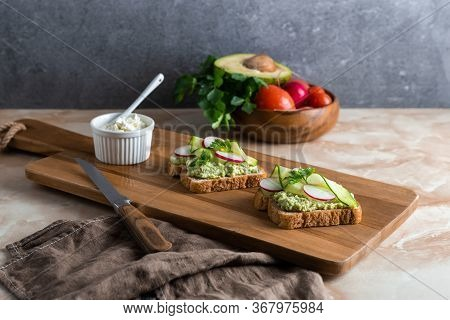 Sandwiches With Radish, Cucumber, Cottage Cheese And Avocado Sauce From Bread Toasts. Close-up Of Tw