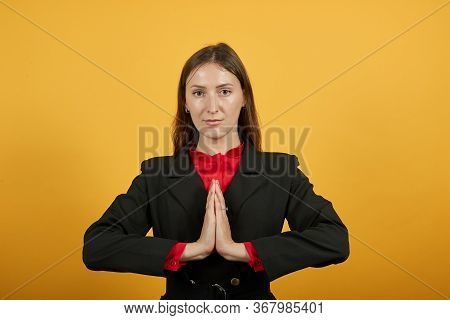 Young Attractive Brunette Woman In Black Stylish Suit, Red Shirt On Yellow Background, Focused Relax