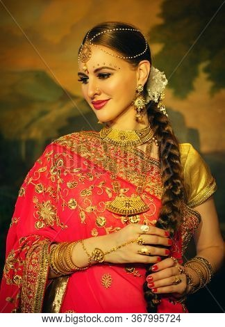 Portrait smiling of beautiful indian girl at home. Young woman model with golden jewelry set .