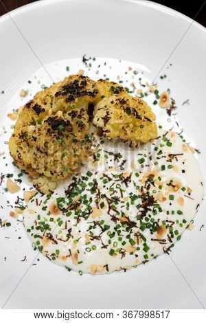 Roasted Cauliflower with Parmesan and Hazelnut topping with spring onion and cauliflower soup, gourmet international cuisine recipe. Restaurant gastronomy food and drink consumerism concept.