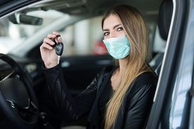 Masked woman showing the key of her new car in a car dealer saloon during coronavirus pandemic