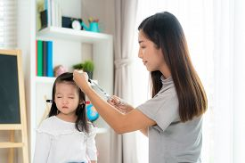 Asian Mother Cutting Hair To Her Daughter In Living Room At Home While Stay At Home Safe From Covid-