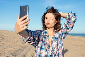 A Cheerful Dark-haired Woman Smiles, Takes A Selfie On The Phone,  Walks Along The Beach,  Enjoys Th