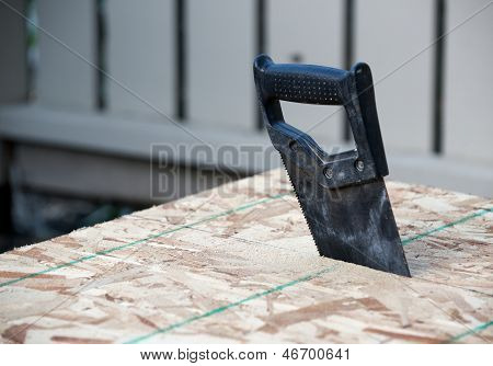 Angled View Of A Hand Saw In Wood