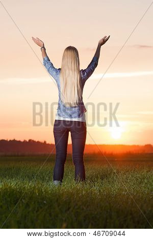 Blonde Woman Lifts Hands Up To The Sun