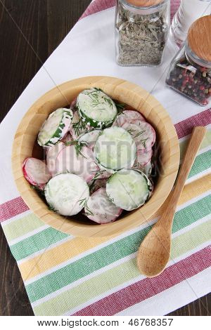 Vitamin vegetable salad in wooden bowl on wooden table close-up