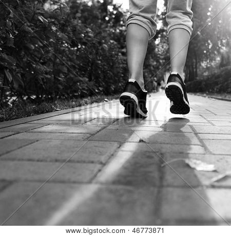 Runner feet running on road closeup on shoes. Woman fitness sunrise jog workout welness concept. Black and white poster