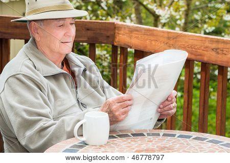 Elderly Man Reading Newspaper and Drinking Coffee