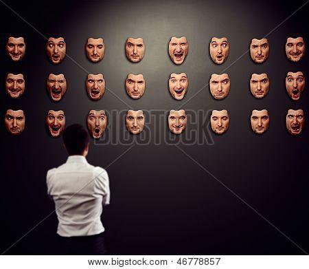 businessman looking at mask and selecting his mood