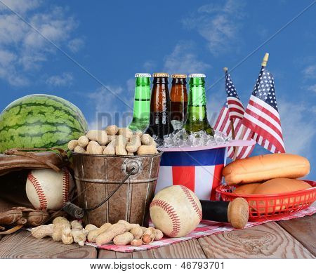 Picnic table ready for a Fourth of July celebration. Cold beer in an Uncle Sam Hat, watermelon peanuts, baseball, and hot dog buns fill the table, with a blue cloudy sky background.