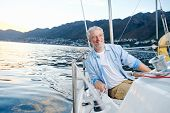 carefree happy sailing man portrait of mature retired man on ocean boat at sunrise poster