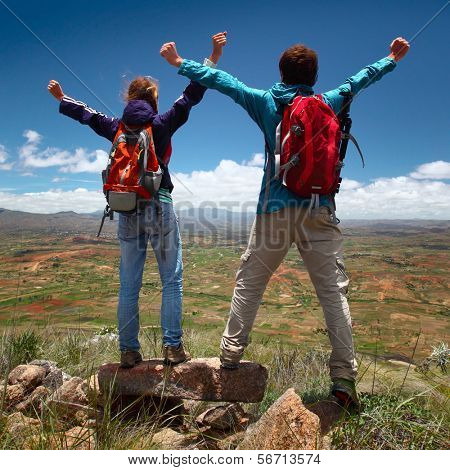 Hikers with backpacks standing on top of a mountain with raised hands poster