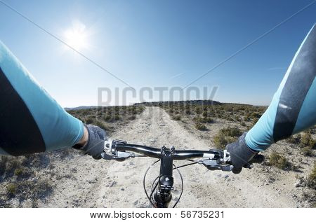 forefront of the handlebars of a bicycle on a walk through a barren landscape