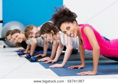 Group Of Fit Young People Doing Push Ups