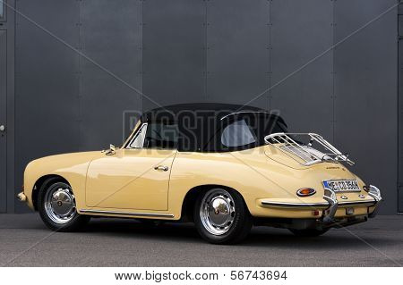 Dusseldorf, Germany - June 17, 2009: A perfectly restored light yellow Porsche 356 C convertible in front of a grey steel wall.