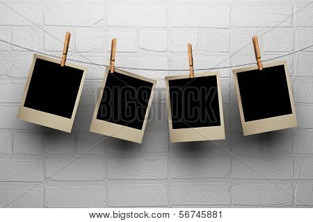 Photos Hanging On Clothespegs Against A Wall
