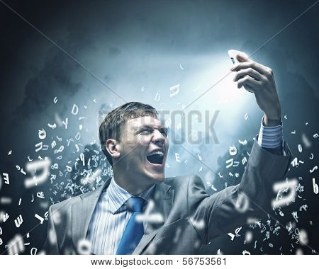 Angry businessman screaming i to mobile furiously phone