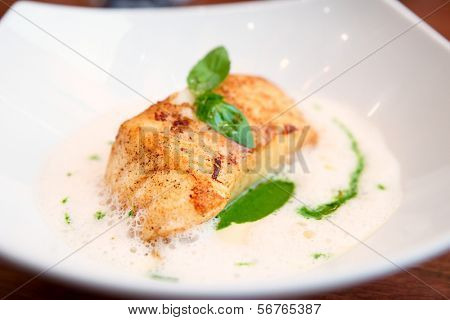 Fried fish fillet with broth sauce on plate