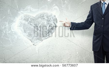 Businessman holding stone in shape of heart in palm
