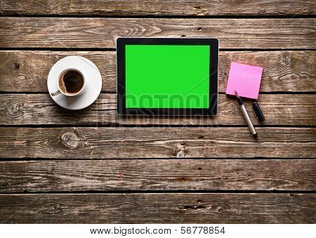 Digital tablet computer with sticky note paper and cup of coffee on old wooden desk. Simple workspace or coffee break with web surfing.