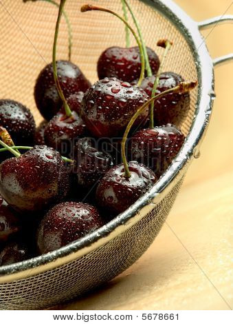 Dark Cherries In Mesh Sieve On Wooden Table
