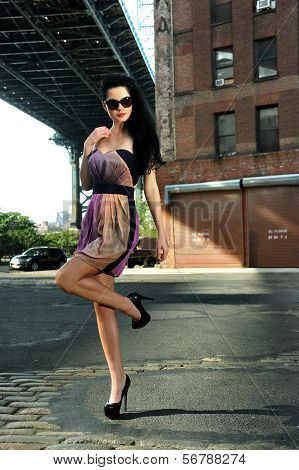 Fashion model standing under Manhattan Bridge