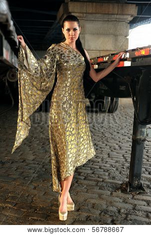 Fashion model posing in long designer evening dress at historical area