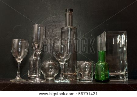 Still Life With Glasses, Bottle And Vase On A Dark Background