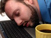 Man falls asleep on his laptop computer. poster