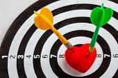 Closeup of black and white target with two dart in red valentine heart love symbol as bullseye. Skeet trap shooting sport in valentines day. poster