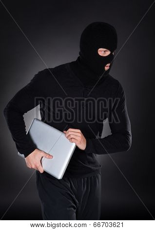 Thief Stealing A Laptop Computer