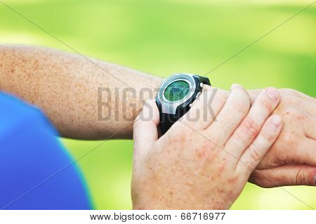 Male runner looking at his heart rate monitor. poster