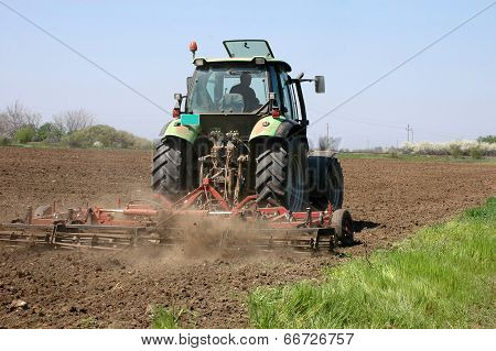 Farming a field with a tractor