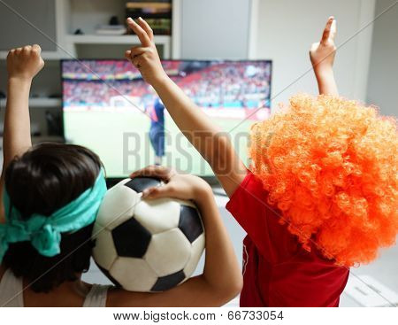 Family with football watching soccer world cup game 2014 on tv in living room