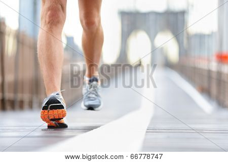 Running shoes, feet and legs close up of runner jogging in action and motion on Brooklyn Bridge, New York City, USA