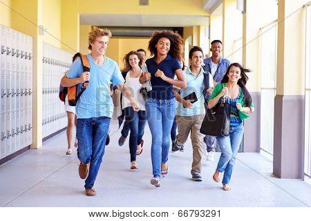 Group Of High School Students Running In Corridor