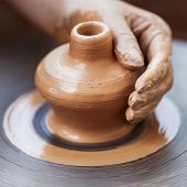 Potter hands making in clay on pottery wheel. Potter makes on the pottery wheel clay pot. poster