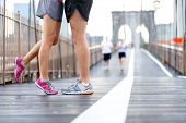 Kissing couple running - Love sport romantic dating concept. Closeup of running shoes and girl standing on toes to kiss boyfriend during jogging workout training on Brooklyn Bridge, New York City, USA poster