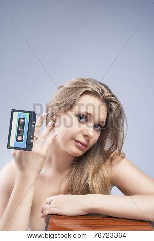 Young Caucasian Blond Woman Playing With Old Audio Tape