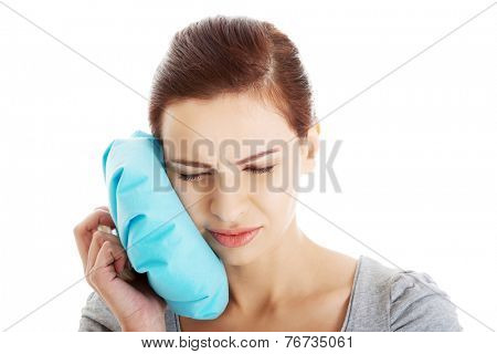 Woman with toothache touching face by icebag.