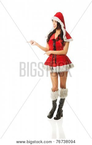 Beautiful slim woman wearing santa clothes and pointing to the left. poster