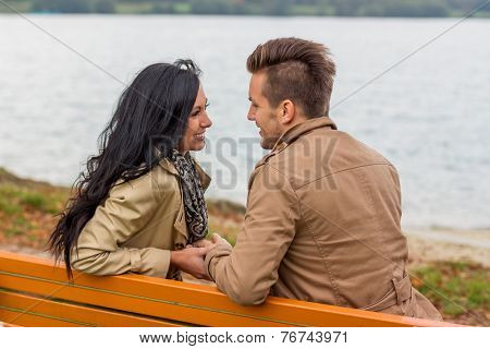 a young, laughed liebtes couple sitting on a park bench