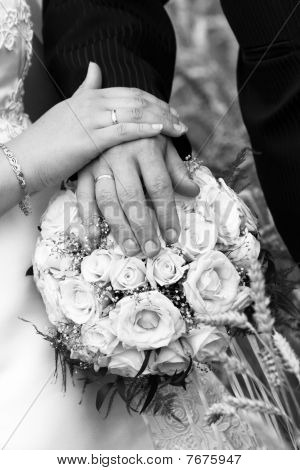 Wedding couple holding hands with wedding bands and flower bouquet