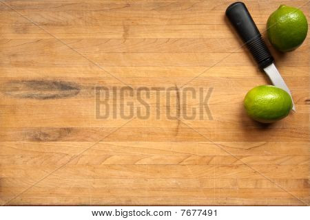 Limes And Knife On Cutting Board