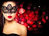 Sexy model woman in venetian masquerade carnival mask at party over holiday glowing red background. Christmas and New Year celebration. Glamour lady poster